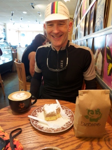 Latte, coffee cake, cheesy grin, beans.
